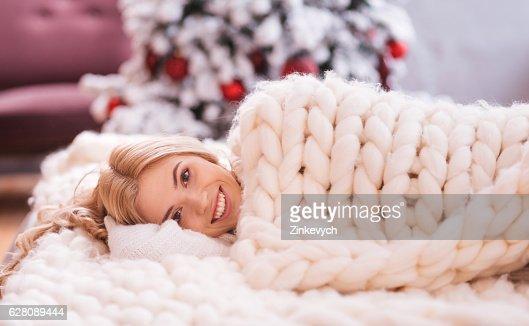 Smiling joyful woman lying under a warm blanket : Stock Photo