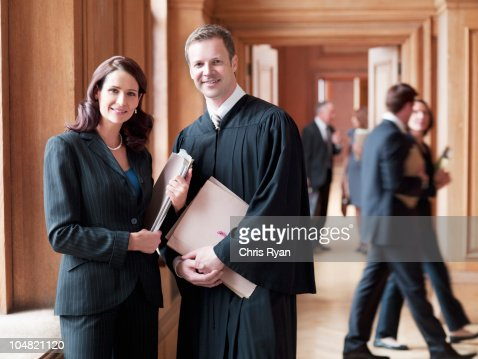 Smiling judge and lawyer in corridor