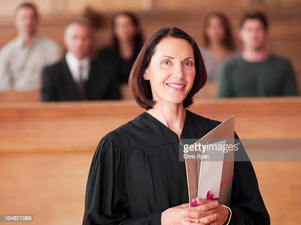 Juiz sorridente segurando o ficheiro na Sala de Tribunal
