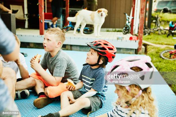 Smiling kids sitting on back porch of home eating hot dogs on summer evening