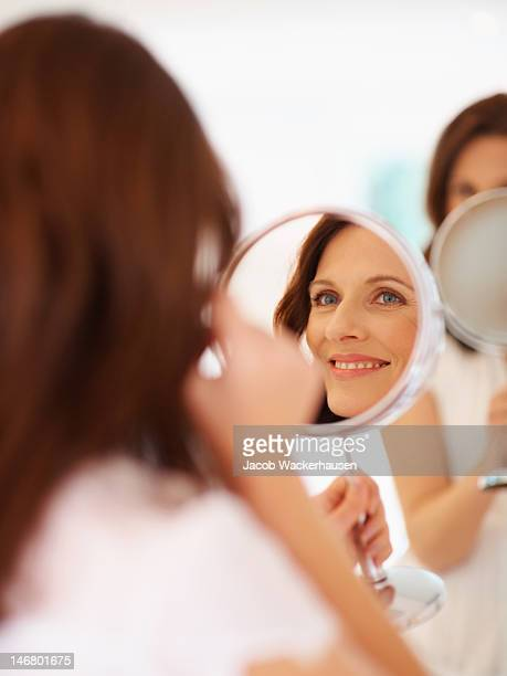 Smiling lady looking at her face in mirror