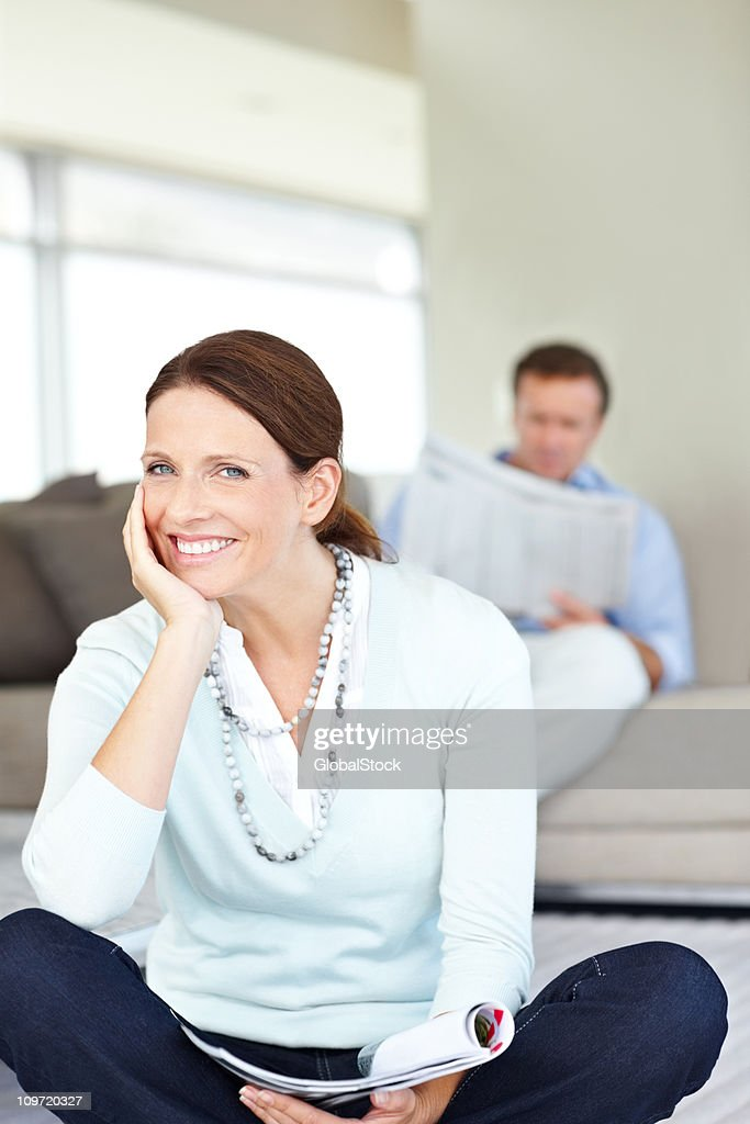 Smiling lady with magazine while man reading newspaper in background : Stock Photo