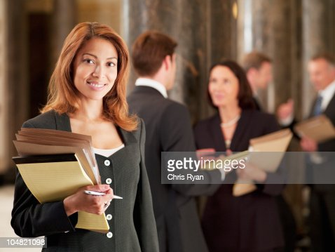 Smiling lawyer holding files in corridor