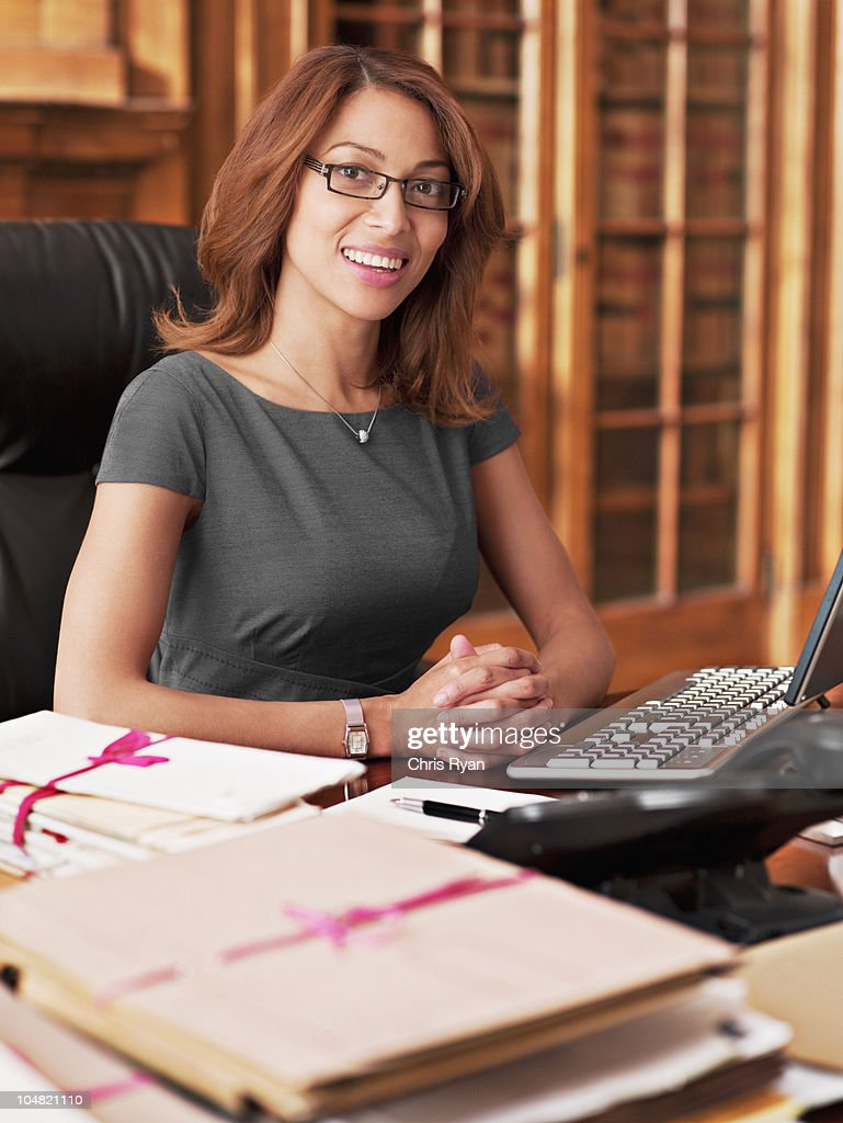Smiling lawyer sitting at laptop in office : Stock Photo