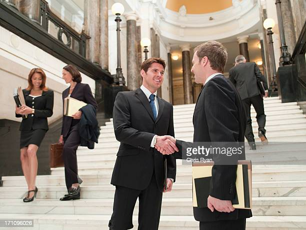 Smiling lawyers shaking hands on stairs