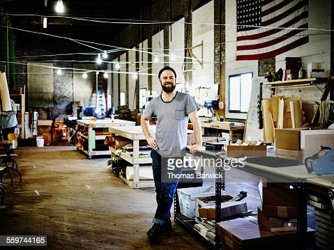 Smiling leatherworker standing in studio