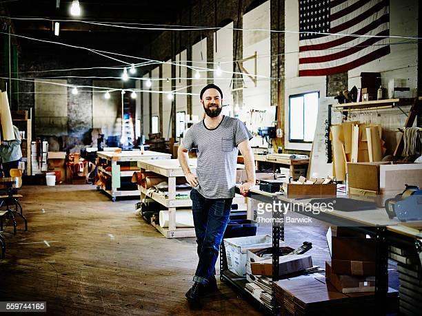 Smiling leatherworker standing in studio