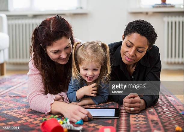 Smiling lesbian couple and girl using digital tablet at home