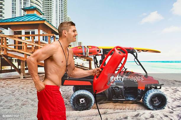 Smiling lifeguard running at the beach