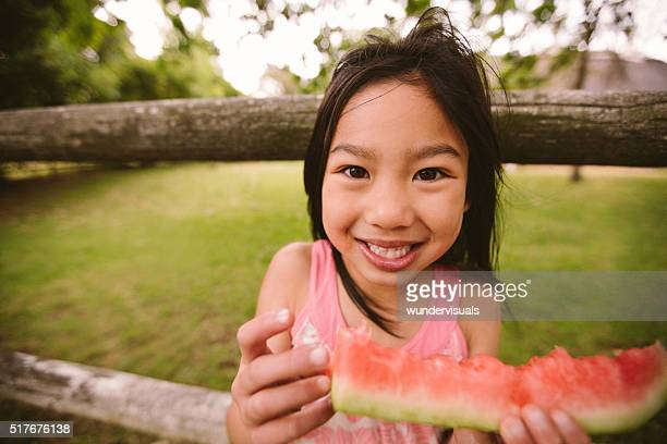 Smiling little asian girl holding slice of watermelon in park