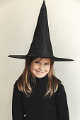 Smiling little blond girl in black witch costume over white wall, close-up studio portrait
