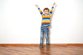 Smiling  little boy holding hands up looking at camera against the background of a white wall.