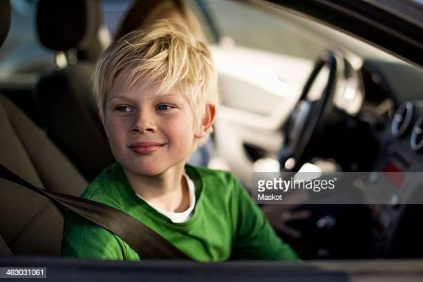 Smiling little boy looking through car window