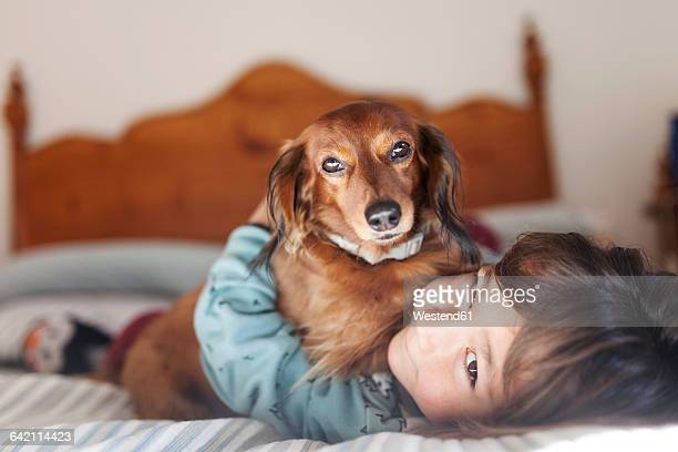 Smiling little boy lying on bed with long-haired Dachshund