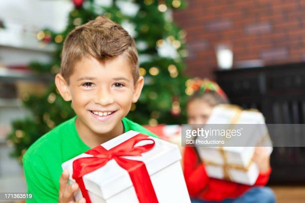 Smiling little boy opening Christmas presents with sister