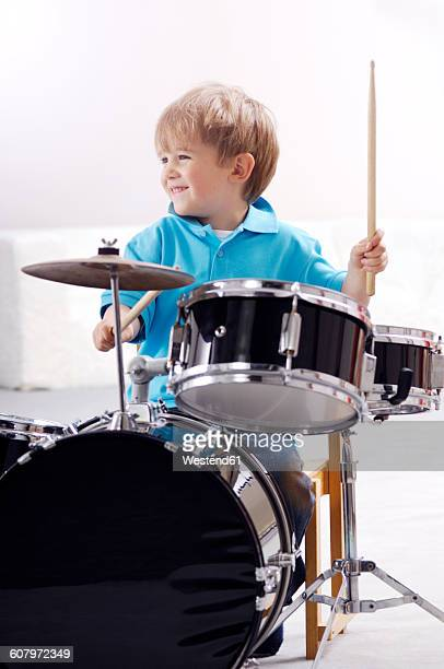 Smiling little boy playing drums