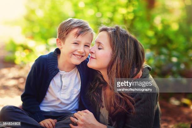 Smiling little boy sitting by his mother