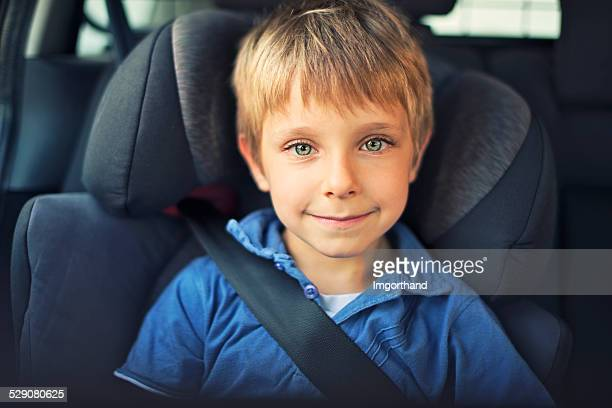 Smiling little boy sitting car in child seat.