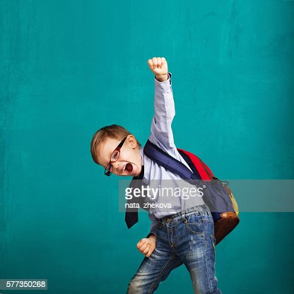 smiling little boy with big backpack jumping and having fun : Stock Photo
