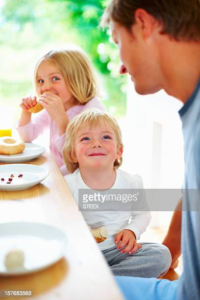 Smiling little boy with his father and sister having breakfast
