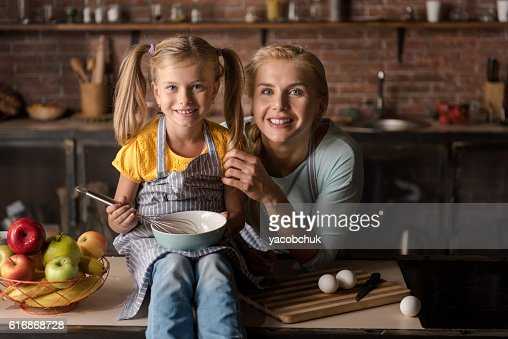 Smiling little daughter cooking with her mother in the kitchen : Stock Photo