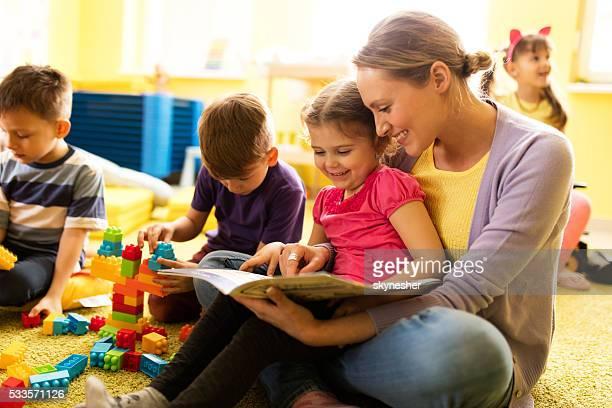 Lächelnd kleines Mädchen und Lehrer lesen eine Geschichte bereits im kindergarten an.