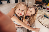 Smiling little girl and woman in kitchen taking selfie. Happy young mother and daughter cooking food.