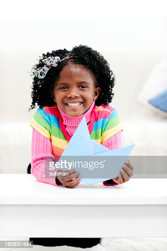 Smiling little girl at home with a paper boat : Stock Photo