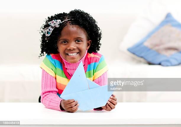 Souriant petite fille à la maison avec un bateau en papier