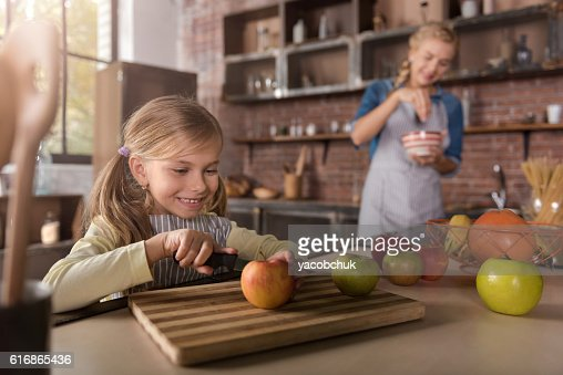 Smiling little girl cutting apples in the kitchen : Stock Photo
