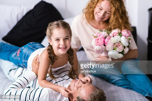 Smiling little girl having fun with her grandfather : Stock Photo