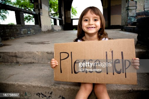 Smiling Little Girl Holding a Please Help Sign