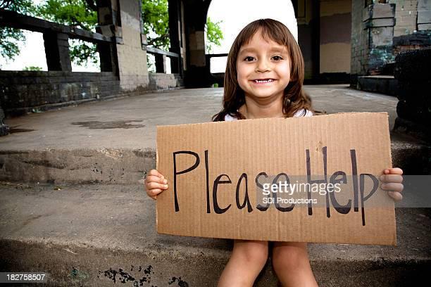 Sorridente bambina che tiene un Cartello Si prega