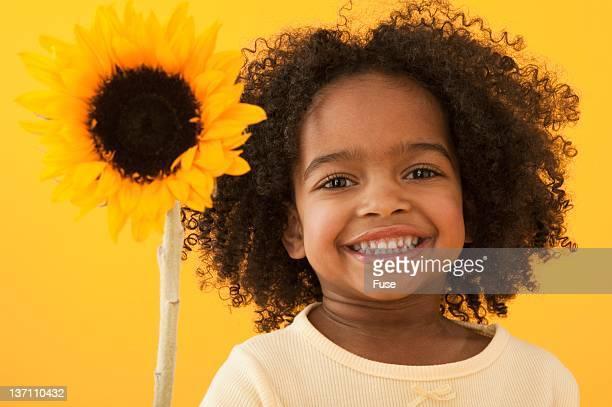 Smiling little girl holding a sunflower