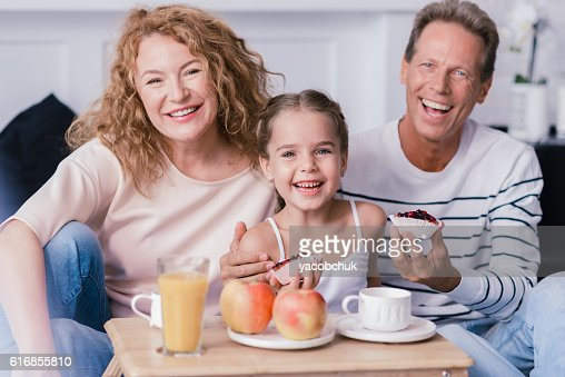 Smiling little girl holding berry cupcakes with her grandparents : Stock Photo