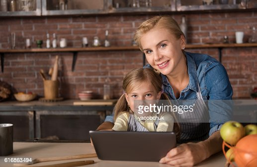 Smiling little girl holding the tablet with her mother : Stock Photo