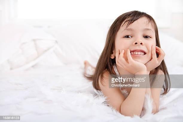 Souriant Petite fille jouant avec des plumes en lit