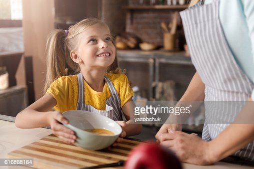 Smiling little girl showing the bowl to her mother : Stock Photo