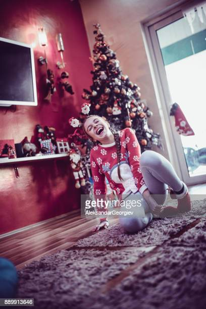 Smiling Little Girl Sitting on Floor by the Christmas Tree at Home