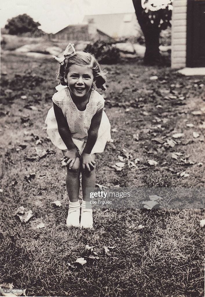 1935, smiling little girl with hands on her knees : Stock Photo