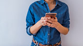 African american person holding a tactile mobile smartphone - Black people. Woman holding smartphone. Close-up image of young hipster girl using modern smartphone device isolated over gray background
