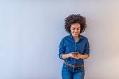 Cheerful African american woman standing isolated over gray background, holding mobile phone. Smiling lovely young woman standing and using cell phone over grey background