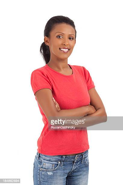 Smiling lovely young woman standing with hands clasped.