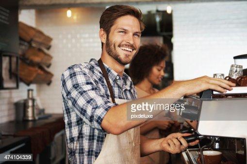 Smiling male barista preparing coffee