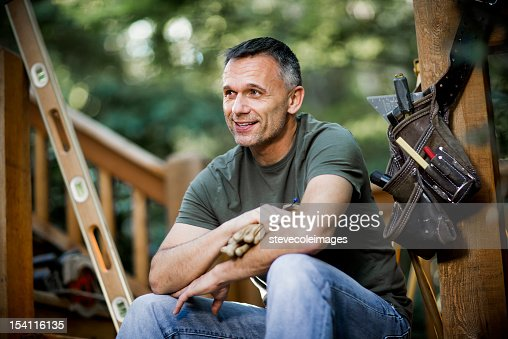 Smiling Male Carpenter With Work Gloves And Tool Belt. : Stock Photo