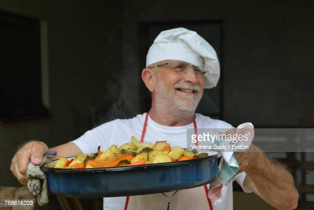 Smiling Male Chef Holding Food In Container
