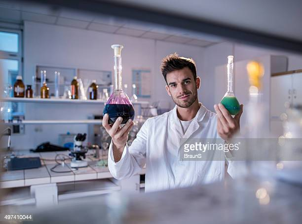 Smiling male chemist with beakers in a laboratory.