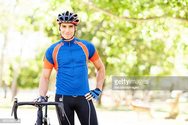 Smiling Male Cyclist Wearing Helmet With Bicycle At Park