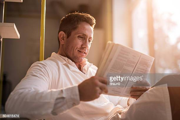 Smiling male doctor relaxing while reading a book.