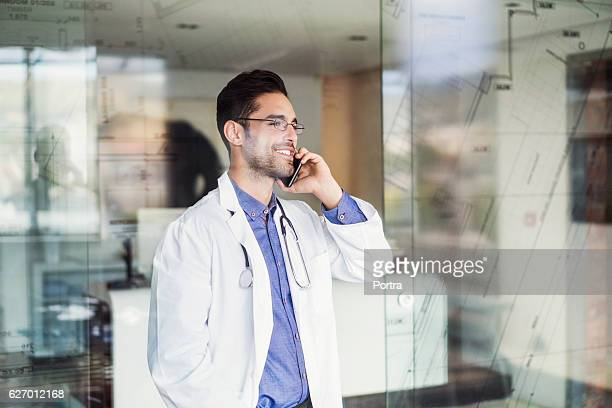 Smiling male doctor using smart phone in clinic